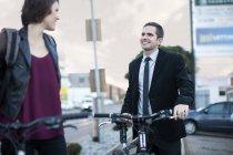 Jovencita charlando con un hombre de negocios mientras anda en bicicleta para trabajar - foto de stock
