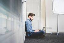 Jovem do sexo masculino sentado no chão do escritório usando laptop — Fotografia de Stock