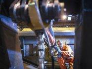 Инженер, осматривающий стальные детали на заводе — стоковое фото