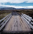 Wooden bridge and dirt road in rural landscape — Stock Photo