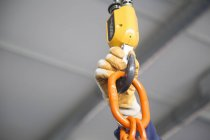 Worker hand adjusting chain hoist in industrial plant — Stock Photo
