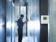 Работник завода с помощью цифрового планшета для проверки энергопотребления на заводе — стоковое фото