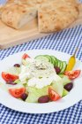 Plate of greek salad with bread on table — Stock Photo