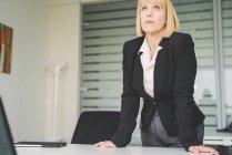 Mujer de negocios madura seria inclinándose hacia adelante en el escritorio de la oficina - foto de stock