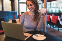Mid adult woman in cafe looking at laptop — Stock Photo