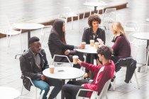 Freunde sitzen an Tischen im Straßencafé und genießen einen Kaffee — Stockfoto