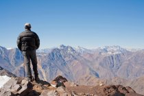 Rear view of hiker overlooking snowy mountains — Stock Photo