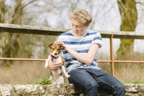 Adolescente, sentado en la pasarela con su gato perro russell - foto de stock