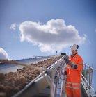 Worker inspecting stone screening and crushing machine in quarry — Photo de stock