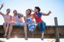 Молодих друзів разом сидячи на пристані, низький кут зору — стокове фото