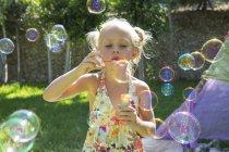 Ragazza soffiando bolle in estate giardino partito — Foto stock