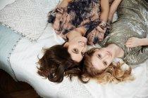 Висока кут портрет двох стильних красиві молоді жінки лежачи на ліжку — стокове фото