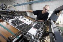 Рабочий контроль печатной машины в типографии — стоковое фото