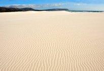 Onduladas de areia na praia com o céu azul nublado — Fotografia de Stock