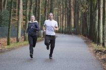 Casal correndo pela floresta — Fotografia de Stock