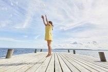 Young girl on wooden pier, jumping to reach bubbles — Stock Photo