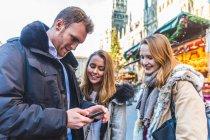 Молодой человек и подруг, глядя на смартфон на Рождественский рынок — стоковое фото