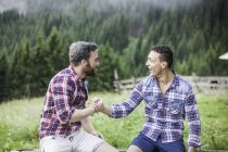 Two male friends shaking hands — Stock Photo