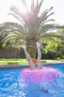 Girl diving into inflatable ring in garden swimming pool — Stock Photo