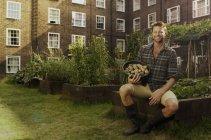 Homem na propriedade do conselho loteamento com tigela de batatas — Fotografia de Stock