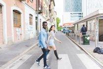 Couple walking across pedestrian crossing, Milan, Italy — Stock Photo