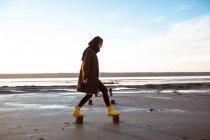 Woman balancing on wooden stumps on beach — Stock Photo