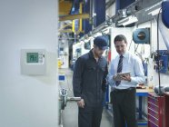 Factory and office workers discussing energy saving in factory — Stock Photo