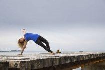 Середине взрослая женщина упражнениями йоги, перейти на деревянных морской пирс — стоковое фото