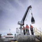 Ingénieurs de parcs éoliens offshore dans le port avec grue — Photo de stock
