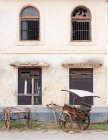 Rickshaw leaning against old colonial building — Stock Photo