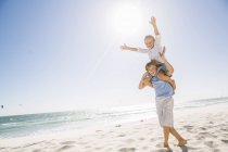 Vue de la pleine longueur de big brother sur plage transportant frère sur les épaules, les bras soulevés souriant — Photo de stock
