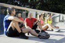 Чоловічі та жіночі бігуни, які беруть перерву і говорять на вулиці — стокове фото