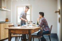 Чоловічий пара, сидячи за столом, маючи їжі — стокове фото
