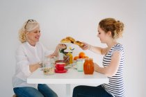 Mother and teenage daughter sharing breakfast — Stock Photo