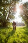 Man riding bicycle in field — Stock Photo