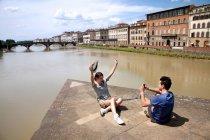 Uomo che fotografa donna con Ponte alle Grazie sullo sfondo, Firenze, Toscana, Italia — Foto stock