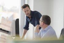 Два офисных работника разговаривают во время работы в офисе за столом с компьютерным монитором — стоковое фото