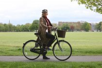 Senior woman riding bicycle in park, portrait — Stockfoto