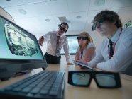 Ingénieurs et apprentis en salle de conférence portant des lunettes 3D pour regarder les écrans 3D — Photo de stock