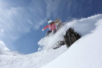 Young female snowboarder jumping off ledge on mountain, Hintertux, Tyrol, Austria — Stock Photo