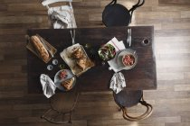 Pork hock, salad and fresh bread on restaurant table, top view — Stock Photo