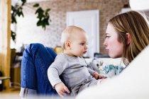 Femme adulte moyenne et petite fille tirant des visages sur le canapé — Photo de stock