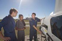 Инструктор полета показывает студентам-пилотам двигатель вертолета — стоковое фото