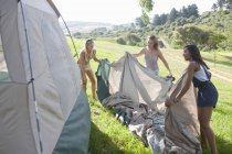 Three young female friends unwrapping tent — Stock Photo