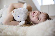 Fille couchée sur un lit à fourrure câlin ours en peluche — Photo de stock