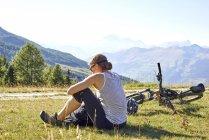 Женская горный байкер, сидя в горный ландшафт, чтение текстов смартфон, Аоста, Аоста, Италия — стоковое фото
