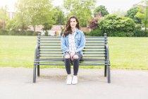 Ritratto di giovane donna seduta sulla panchina del parco — Foto stock