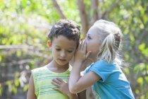 Маленькая девочка шепчет мальчику в саду — стоковое фото
