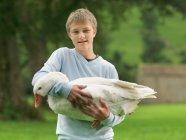 Boy Holding Goose на ферме — стоковое фото