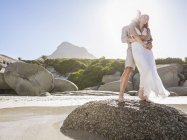Full length view of couple standing on rocks hugging — Stock Photo
